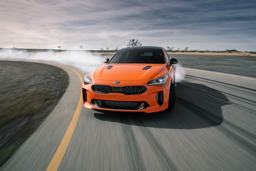 A photo of the 2020 Kia Stinger GTS drifts around a turn on a race track.