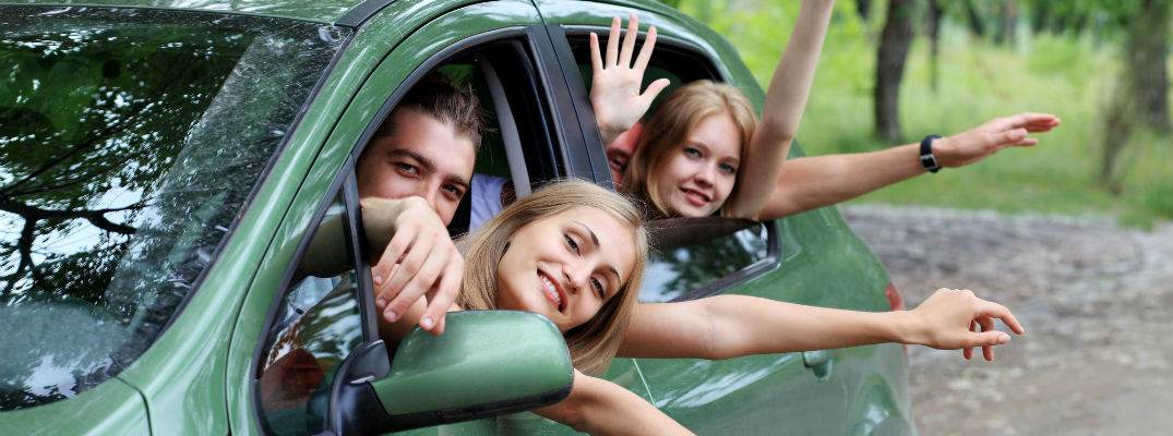 A stock photo of young people hanging out the window of a car.