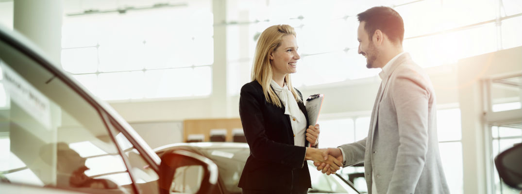 A stock photo of a sales person helping a customer.