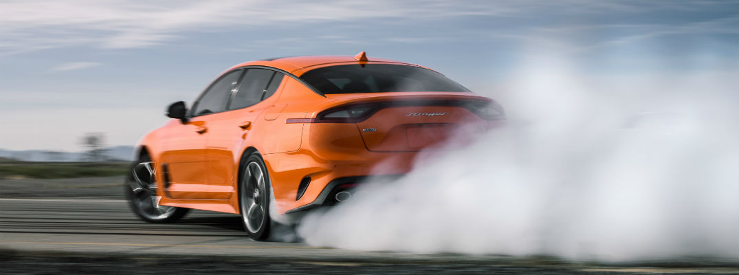 A photo of the 2020 Kia Stinger GTS doing a burnout.