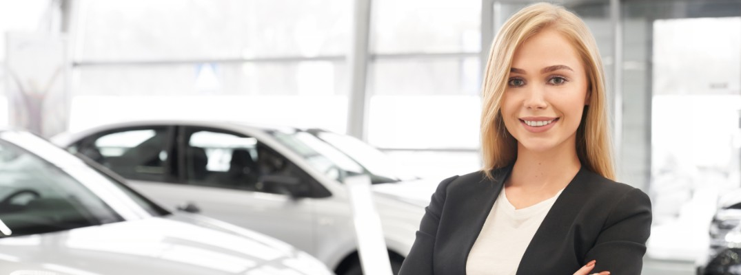 A stock photo of a sales person in a dealership's showroom.