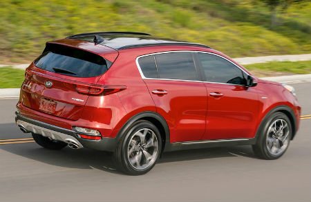 2020 Kia Sportage exterior back fascia passenger side on road with grass and sidewalk