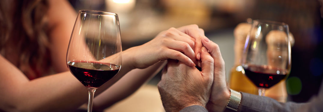 Man and woman holding hands with wine glasses
