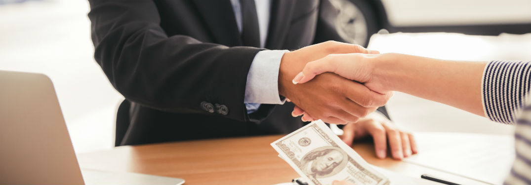 Woman shaking mans hand over table with cash