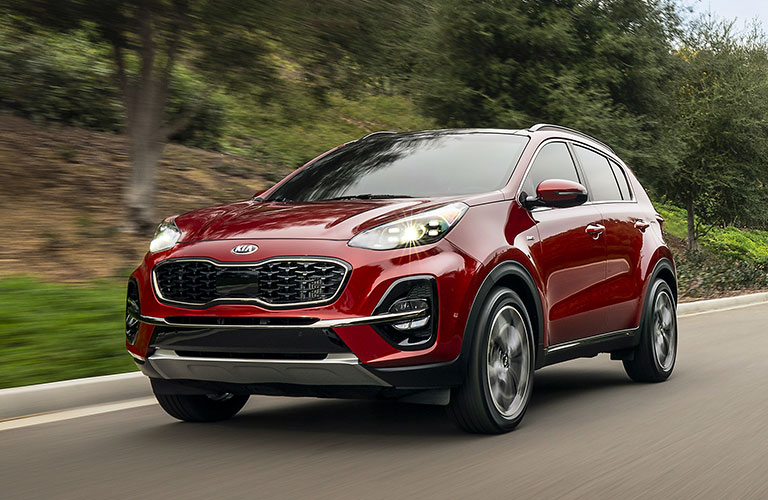 2020 Kia Sportage exterior front fascia driver side on road with blurred trees