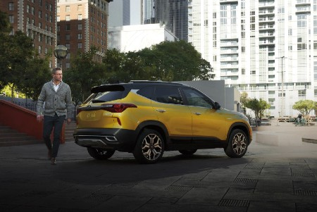 2021 Kia Seltos exterior rear fascia passenger side in city with man walking behind it