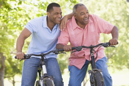 Father and son on bikes with blurred tree background