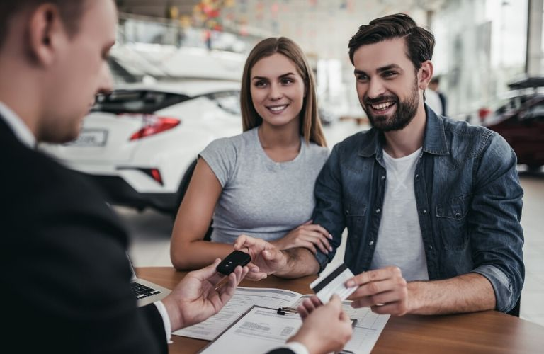 Couple purchasing car with salesman assisting