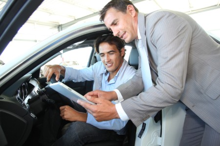 salesman-showing-paperwork-to-car-shopper-in-car
