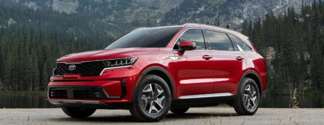 Red colored 2021 Kia Sorento Hybrid with mountains at the back