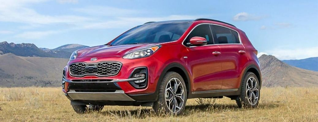 2022 Kia Sportage parked over a grass land with mountains in background