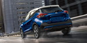 2018 Nissan Kicks driving in a city through with water on the road