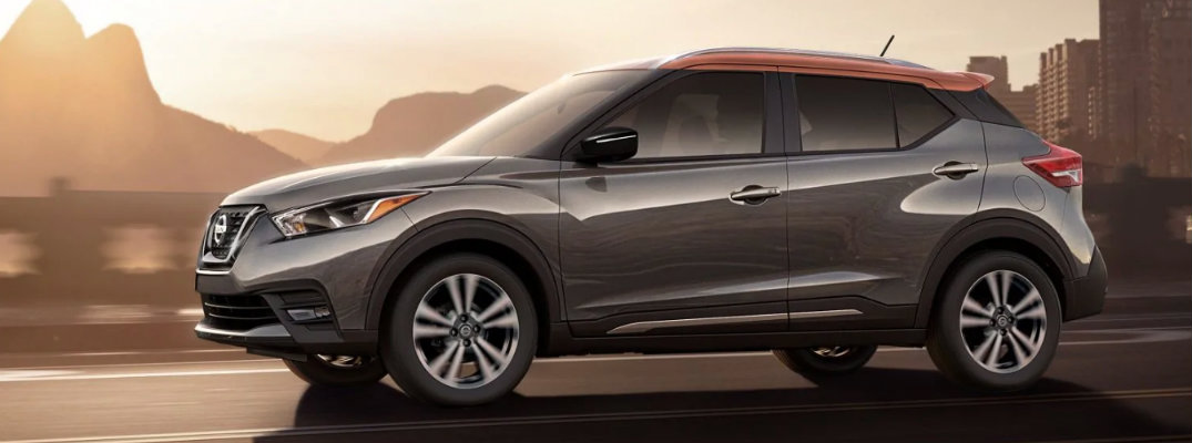 2019 Nissan Kicks exterior side shot with gun metallic and monarch orange paint color driving down a city highway as the sun sets