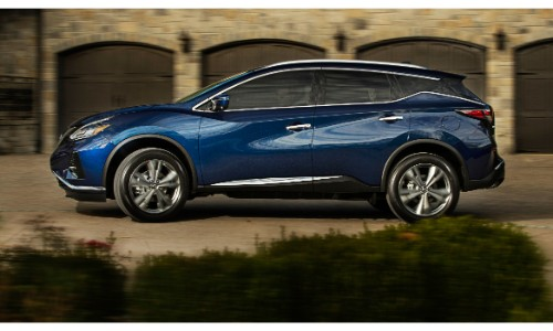2019 Nissan Murano exterior side shot with dark blue paint color parked in front of a line of old fashioned, brick garages