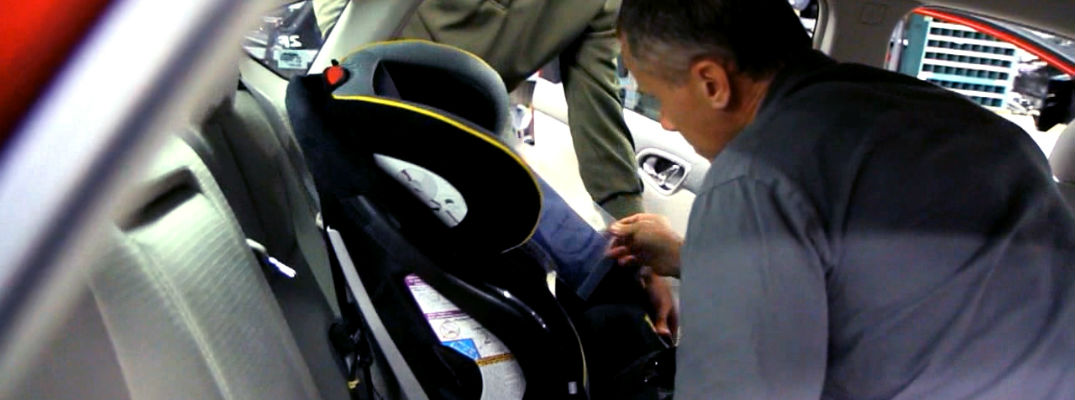 A photo of a person installing a car seat in a Nissan sedan.