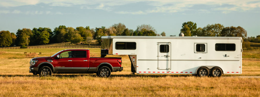A left profile photo of the 2020 Nissan Titan XD pulling a trailer.