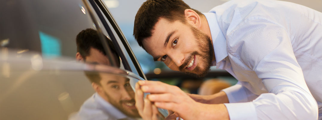 A stock photo of a person looking at a new vehicle.