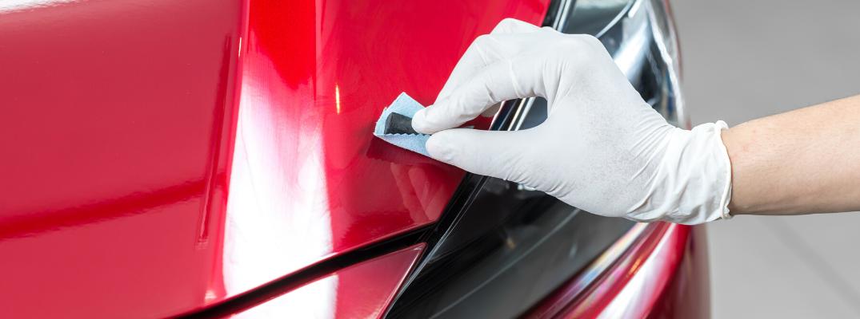Hand polishing a car's hood with sandpaper