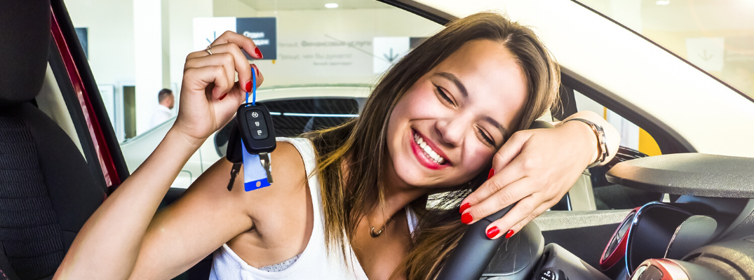 Teenage girl smiling with car keys on hand sitting on driver's seat