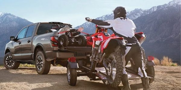 Man Loading a Dirt Bike into the Bed of a 2020 Nissan TITAN