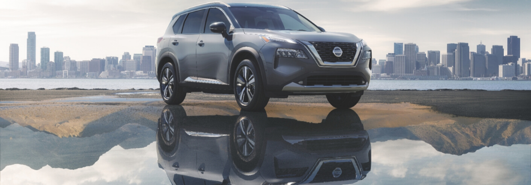 Gray 2021 Nissan Rogue Next to Water with City Skyline in the Background