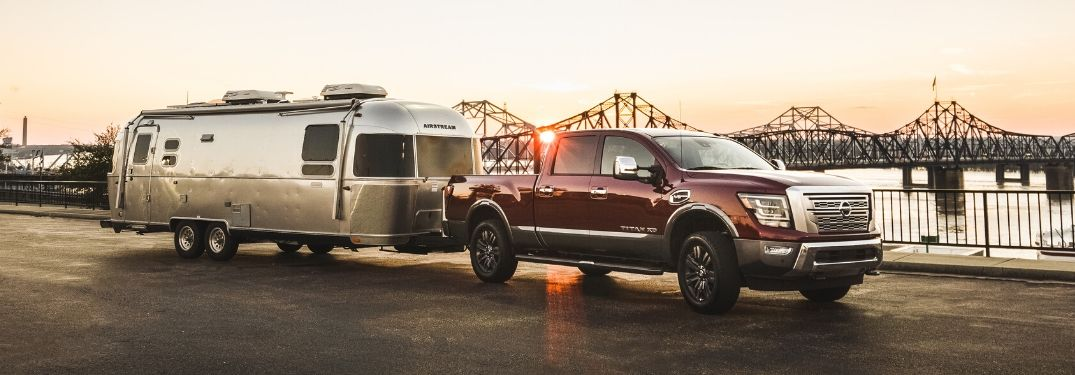 Red 2020 Nissan Titan Towing a Trailer at Sunset