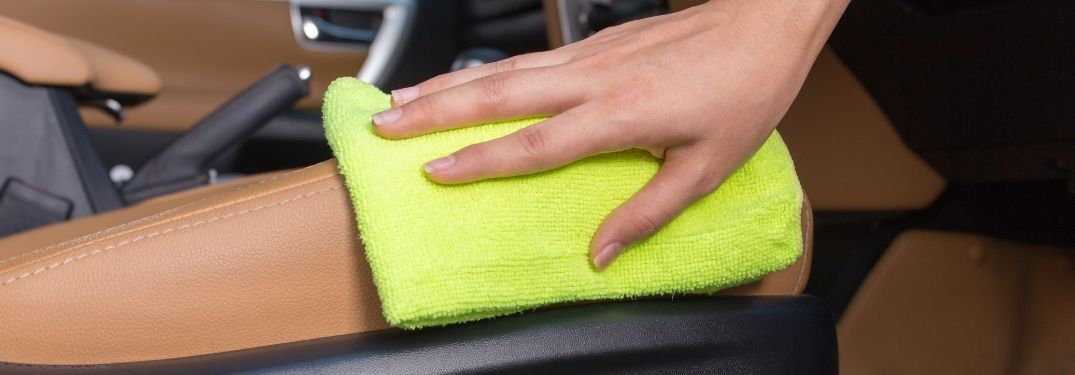 Woman Cleaning Leather Car Interior with Yellow Cloth