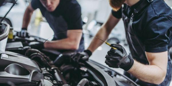 Two auto mechanics working on vehicle