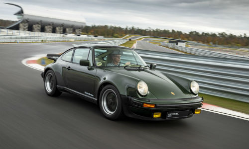 Green historic Porsche 911 model driving on track