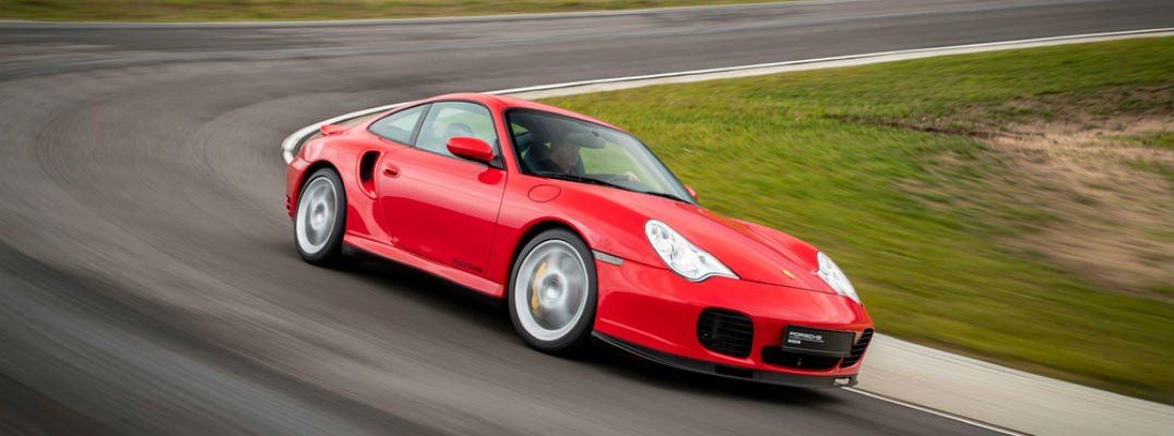 Red historic Porsche 911 driving on track