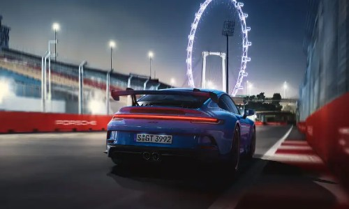 Rear view of blue 2021 Porsche 911 GT3 in front of ferris wheel