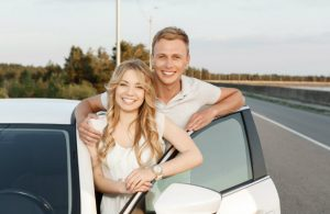 happy couple standing outside of white car