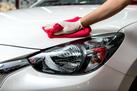 person waxing a car while wearing a disposable glove