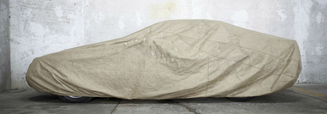 How to Store a Porsche for the Winter with an image of a covered car in a garage
