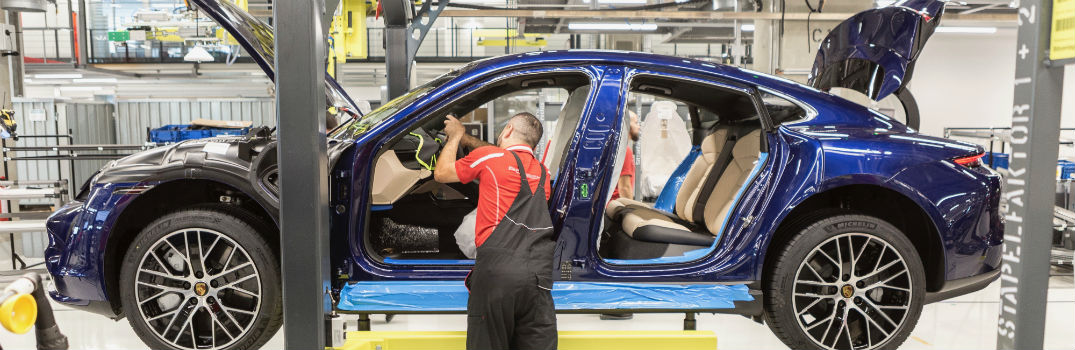 man working on production of Porsche Taycan in Porsche factory