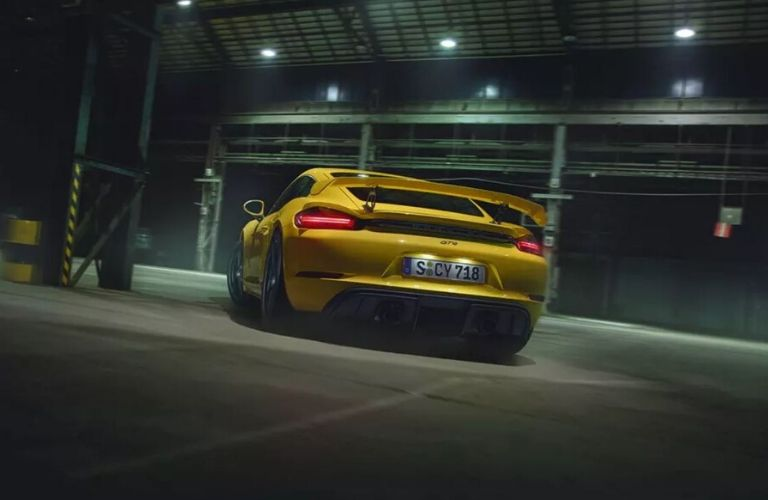 Exterior view of the rear of a yellow 2020 Porsche 718 Cayman GT4