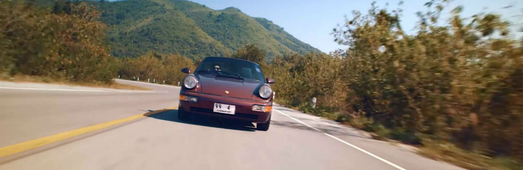 1990 Porsche 964 driving on a road