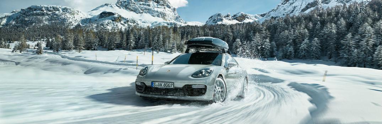 Porsche model with roof mount driving through snowy terrain