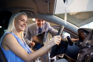 woman in car with car salesman leaning in