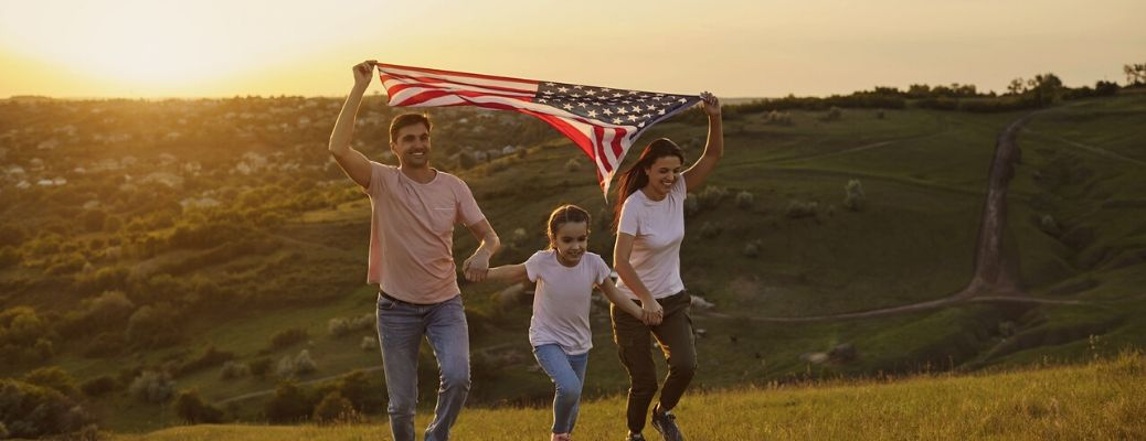 Father mother and daughter holding American flag running up hill