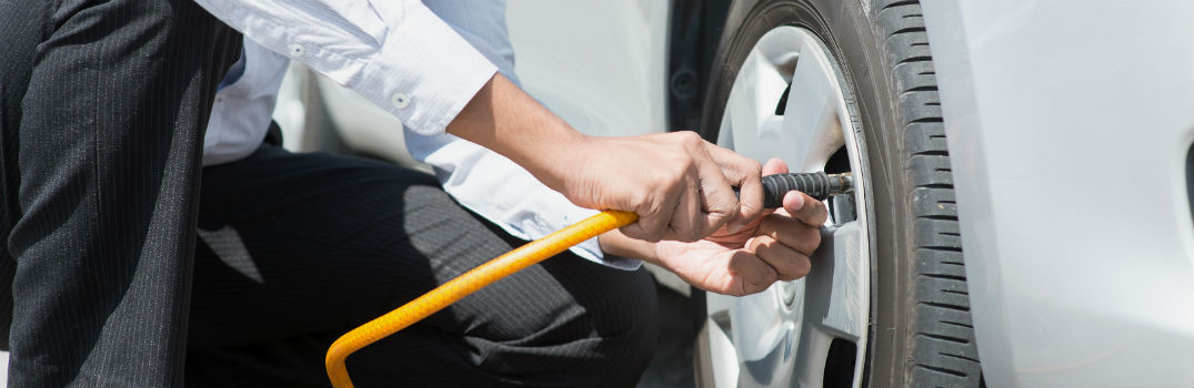 man checking tire pressure in a car