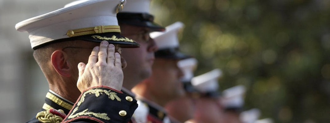 A stock photo of a line of United States Marines saluting a ceremony.