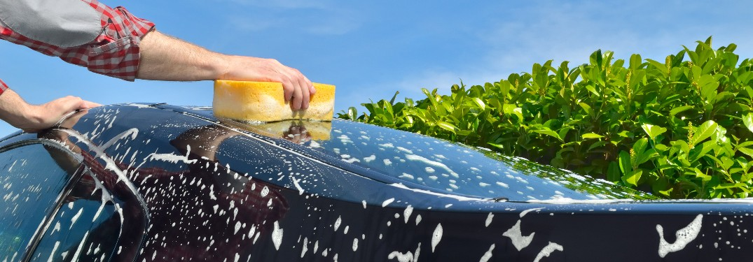 Person with a sponge on top of a suds covered vehicle