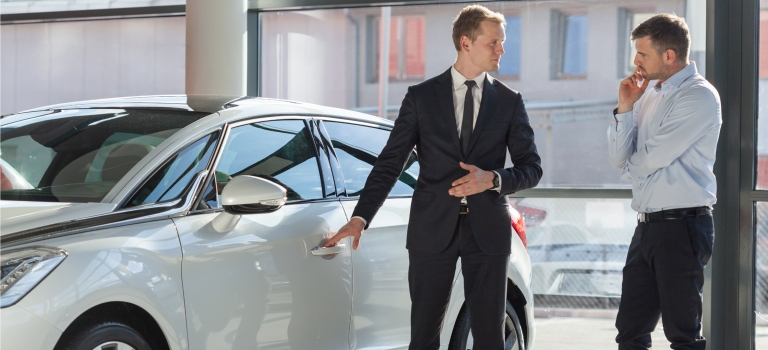 Car salesman showing off a car to a client