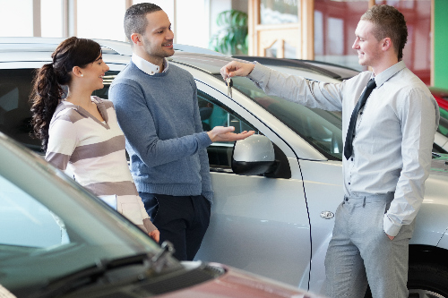 Car salesman handing keys over to a happy couple