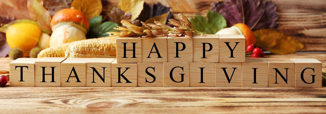 Wooden blocks spelling Happy Thanksgiving on a table filled with food