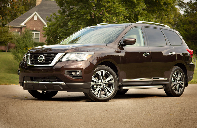 2019 Nissan Pathfinder parked on the street in front of a large house