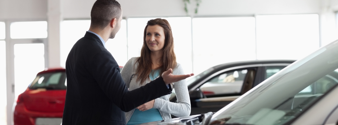 Salesman talking to woman in front of vehicle