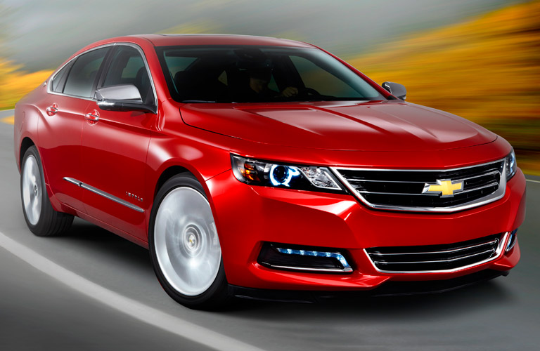 Stylized red 2014 Chevrolet Impala driving fast along a highway surrounded by blur, exterior angled front view.
