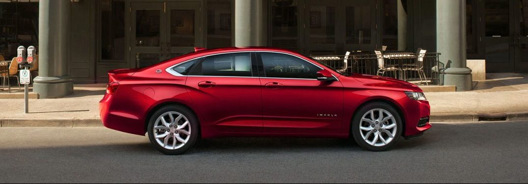 Red 2019 Chevy Impala parked on the side of a city street. Side view.